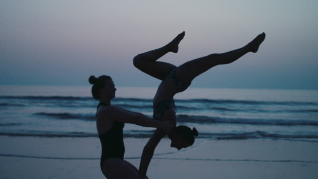 Two beautiful young women practicing Acroyoga on the beach at dusk.