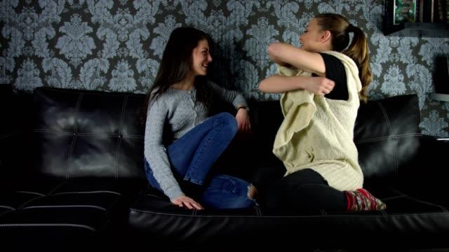 Deux belles jeunes femmes parler avec passion de commérages et rire sur le canapé