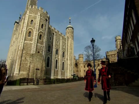 stockvideo's en b-roll-footage met two beefeaters walk past the tower of london - yeomen warder