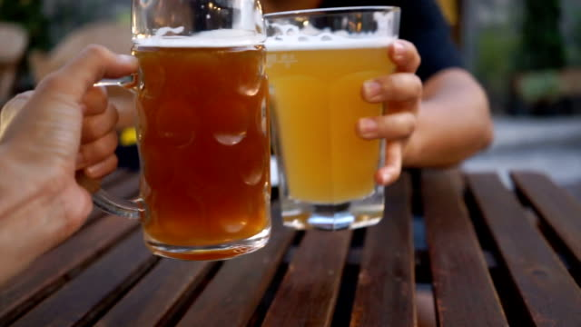 two beer mugs clinked in restaurant. - pint glass stock videos & royalty-free footage