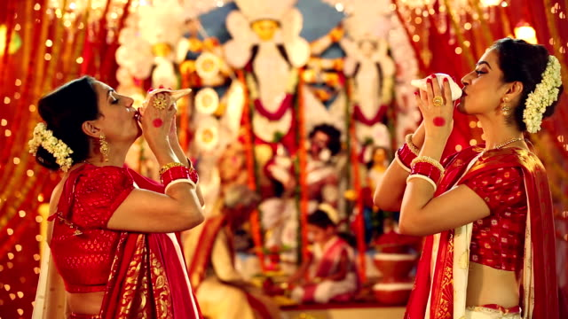 Two bengali women blowing conch shell in durga puja festival, Delhi, India
