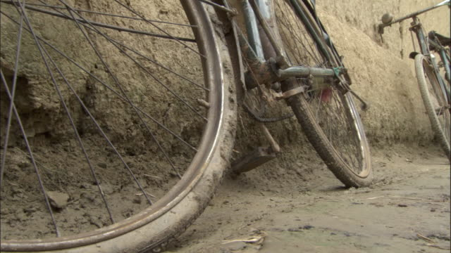 Two bicycles leaning against wall. Uttar Pradesh Available in HD.