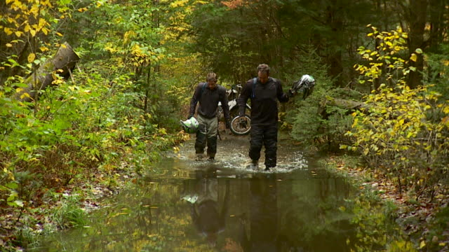 SLO MO WS Two bikers walking through deep puddle, removing helmets / Stowe, Vermont, USA