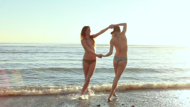 vídeos y material grabado en eventos de stock de ms ts two bikini girls dancing and enjoying at beach / laguna beach, california, united states - laguna beach california