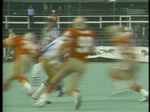 1983 WS ZI Two Birmingham Stallions players tackling quarterback Fred Besana of USFL team Oakland Invaders on field during game / USA