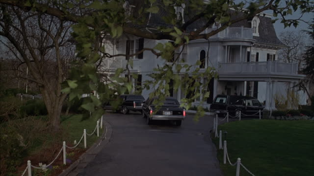 two black cadillacs join a hearse in the driveway of a large white victorian house. - hearse stock videos & royalty-free footage