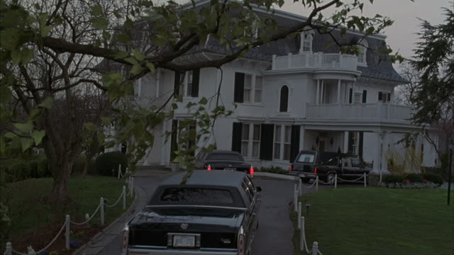 Two black Cadillacs join a hearse in the driveway of a large white Victorian house.