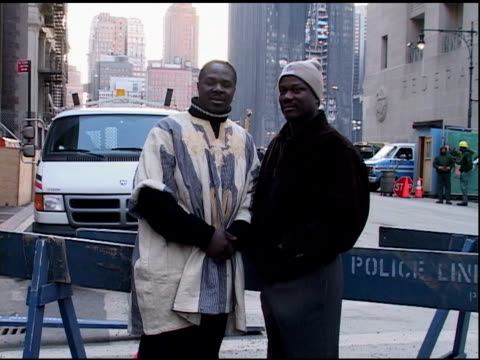 two black male tourists pose at police barricade with ground zero in bg, december 30, 2001. - barricade stock videos & royalty-free footage