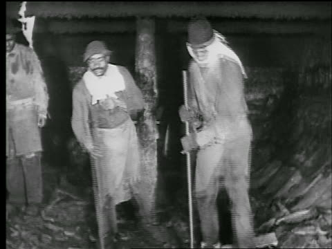 b/w 1929 two black men scrape + pound hardened tar in coal furnace in factory / slate at end / news. - 1920 1929 stock videos & royalty-free footage