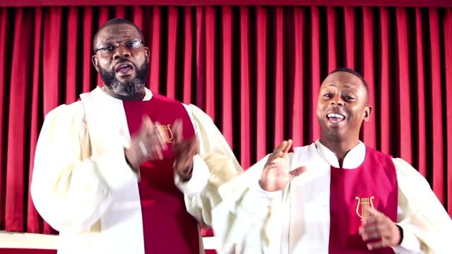 stockvideo's en b-roll-footage met twee zwarte mannen het dragen van gewaden, zingen in de kerk - gospelmuziek