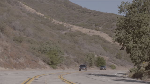 ts two black suvs driving down a mountain road / los angeles, california, united states - sports utility vehicle stock videos & royalty-free footage