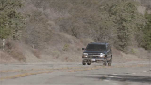 stockvideo's en b-roll-footage met ts two black suvs speeding along a mountain road / los angeles, california, united states - sports utility vehicle