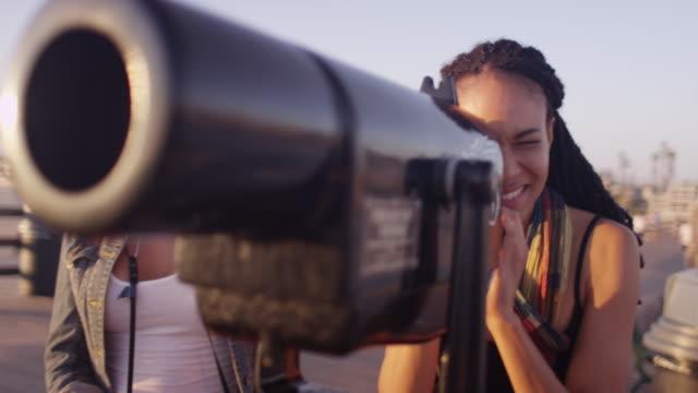 stockvideo's en b-roll-footage met two black woman best friends looking through telescope on pier - westelijke verenigde staten