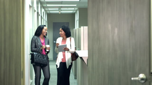 two black women conversing, walking down office hallway - office partition stock videos & royalty-free footage