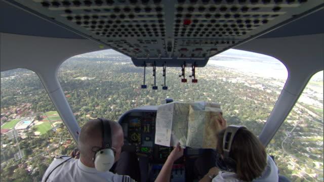 two blimp pilots examine a map. - 飛行船点の映像素材/bロール