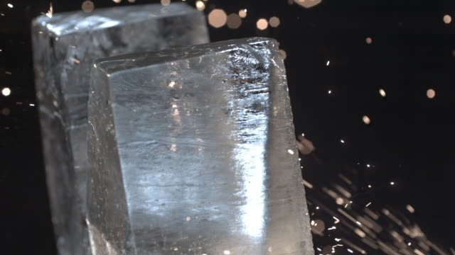 vídeos de stock e filmes b-roll de cu slo mo two blocks of ice with sparks flying around them / united kingdom - dois objetos