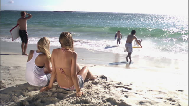 ms two blonde girls chatting while their four male friends playing with body boards behind them on shore / cape town, western cape, south africa - newoutdoors stock videos & royalty-free footage