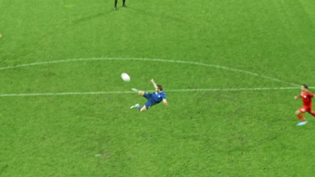 aerial two blue football players celebrating after one scores a goal - tor konstruktion stock-videos und b-roll-filmmaterial