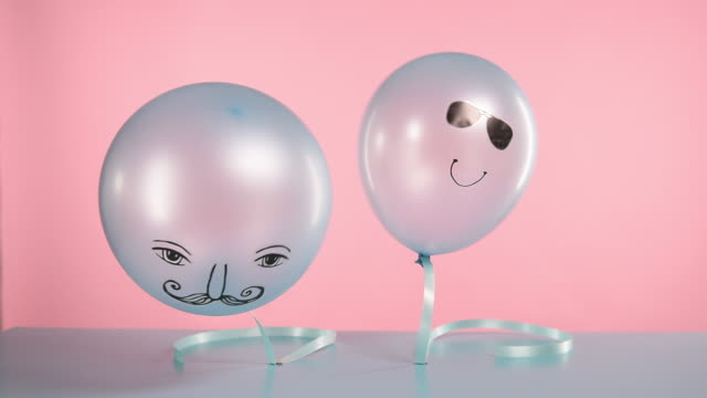 two blue helium balloons with faces
