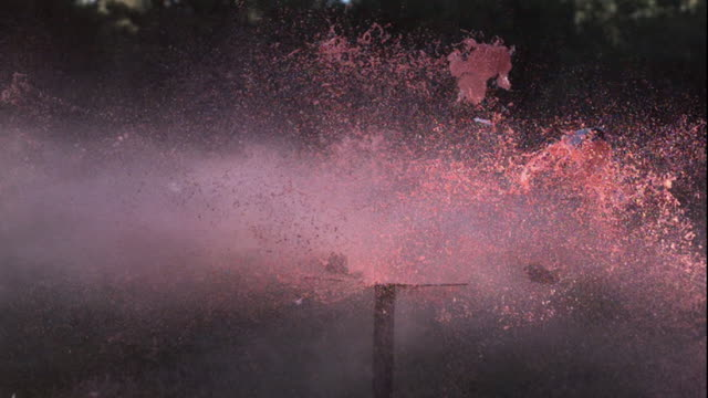two blue milk cartons explode into pink smoke. - letterbox stock videos & royalty-free footage