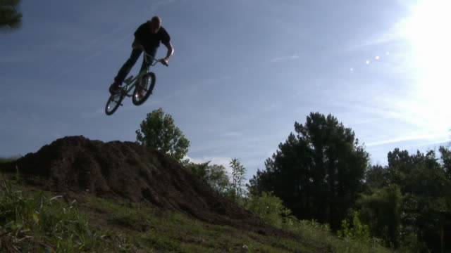 slo mo ws two bmx bikers jumping over hill / jacksonville, florida, usa - freestyle bmx stock videos and b-roll footage