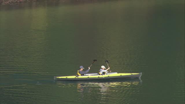 vídeos y material grabado en eventos de stock de aerial two boaters rowing a kayak on walden pond / concord, massachusetts, united states - simetría
