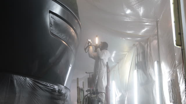 Two boatyard workers wearing protective clothing spray paint a big boat indoors at boatyard
