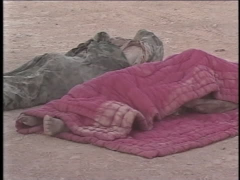 two bodies lie on the ground, wrapped in blankets. - al fallujah stock videos & royalty-free footage