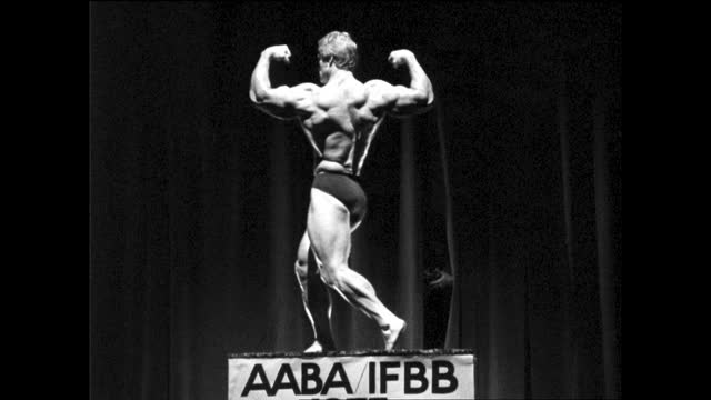 """two body builders posing on stage standing on top of banner """"aaba ifbb 1975 mr. san francisco""""; person taking photos through the curtains - カーテン レース点の映像素材/bロール"""