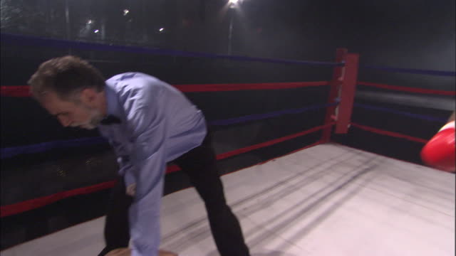 vidéos et rushes de sm ms td pan two boxers fighting in ring, then one gets knocked out and referee counts him out as other boxer celebrates / jacksonville, florida, usa - ring de boxe