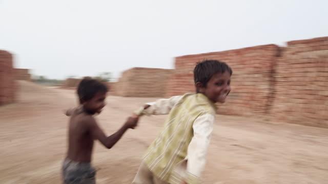 Two boy kids playing at brick factory, Haryana, India