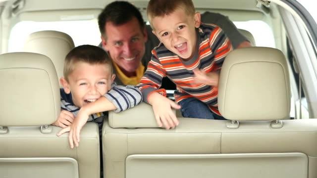 Två pojkar och far klättra in i bilen, skratta åt kameran