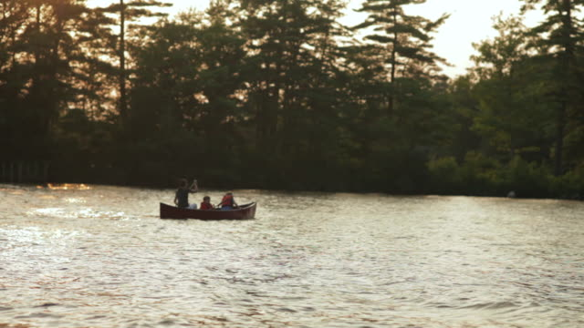 ws two boys and mother canoeing boat in lake / wolfebro, nh, usa      - andare in canoa video stock e b–roll