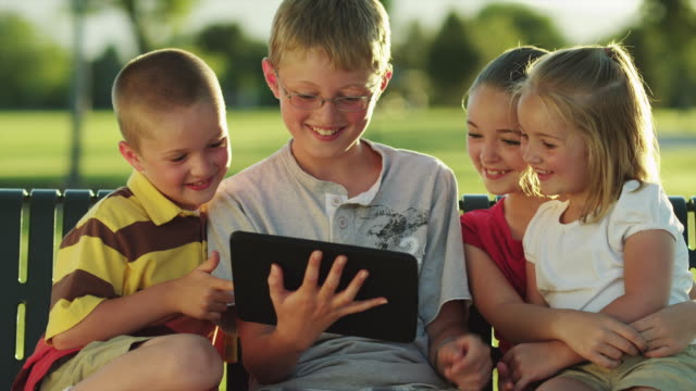 MS ZO Two boys (6-13) and two girls (4-11) using digital tablet, sitting park bench / Orem, Utah, USA
