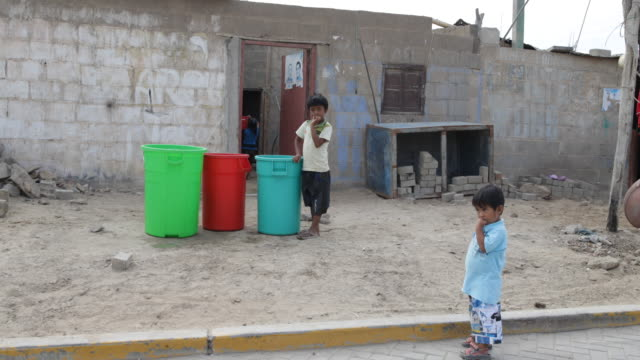 two boys are standing in front of a house next to colorful cans while a girl is carrying a bucket of water in an open house in tortuga peru - south pacific ocean stock videos & royalty-free footage