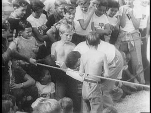 two boys boxing while bob hope referees / hope tries to break up the fight and gets hit /crowd of boys on fence cheers/ hope falls down in ring/ boy... - bob hope komiker stock-videos und b-roll-filmmaterial