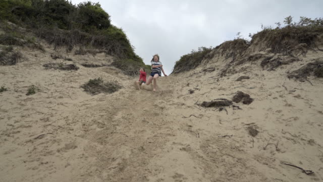 Two Boys, brothers, jumping down sand dunes on the beach.
