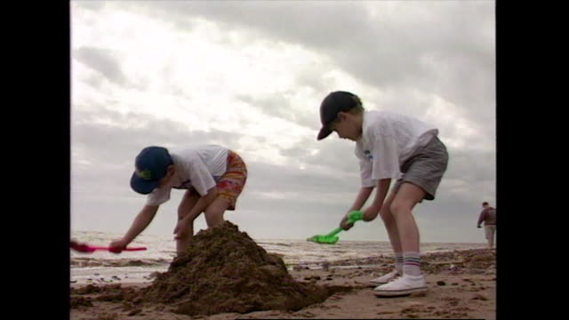 two boys build sandcastles on a sandy beach; 1996 - hat stock videos & royalty-free footage