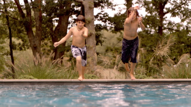 SLO MO WS two boys canonball diving into water/Connecticut, USA