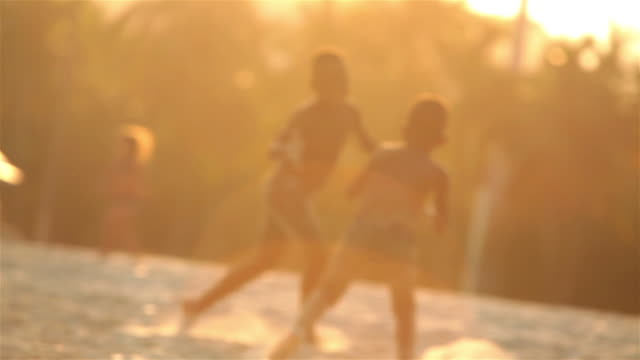 vídeos de stock, filmes e b-roll de two boys chase each other with sandy hands in the sun on brazilian beach - irmão
