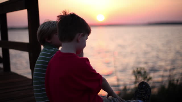 vídeos de stock, filmes e b-roll de two boys chat while watching the colorful sky and rippling ocean. - wilmington carolina do norte