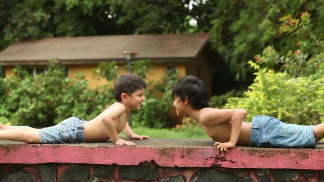 vídeos y material grabado en eventos de stock de two boys doing pushups in a park  - entrenamiento sin material