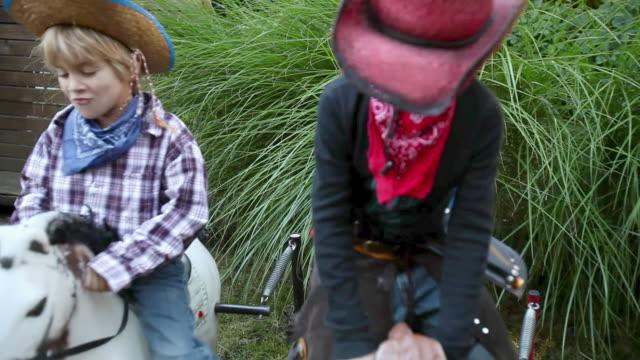 stockvideo's en b-roll-footage met two boys dressed as cowboys on rocking horses - alleen jongens