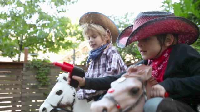 two boys dressed as cowboys on rocking horses with toy guns - toy gun stock videos & royalty-free footage
