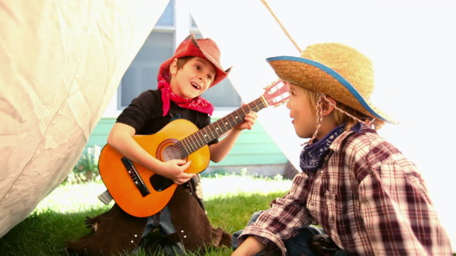 Two boys dressed as cowboys singing and playing guitar