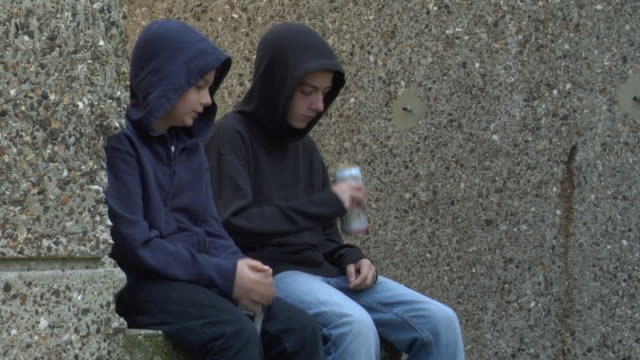 MS Two boys drinking beer and hard alcohol and sitting on steps / London, England