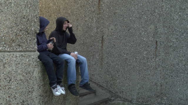 ws two boys drinking beer and hard alcohol and sitting on steps / london, england - hooligan stock videos & royalty-free footage