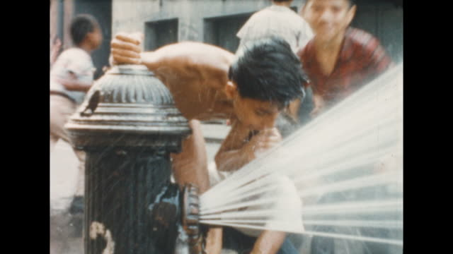 vídeos y material grabado en eventos de stock de of two boys drinking water from an opened fire hydrant while other boys make faces in the background. from the collection of world-famous still... - boca de riego