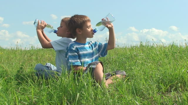 stockvideo's en b-roll-footage met two boys drinking water in hot summer day - drinkwater