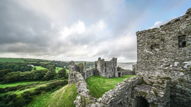vídeos de stock e filmes b-roll de two boys exploring llansteffan castle, wales, in a time lapse. - país de gales